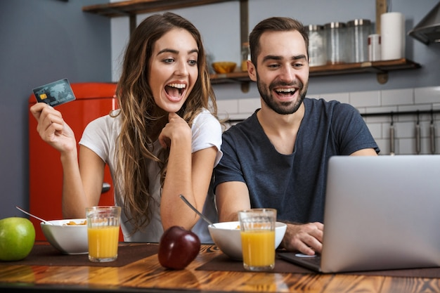 Beautiful cheerful couple having breakfast at the kitchen, using laptop computer, showing credit card