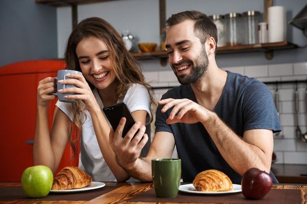 Beautiful cheerful couple having breakfast at the kitchen, using mobile phone
