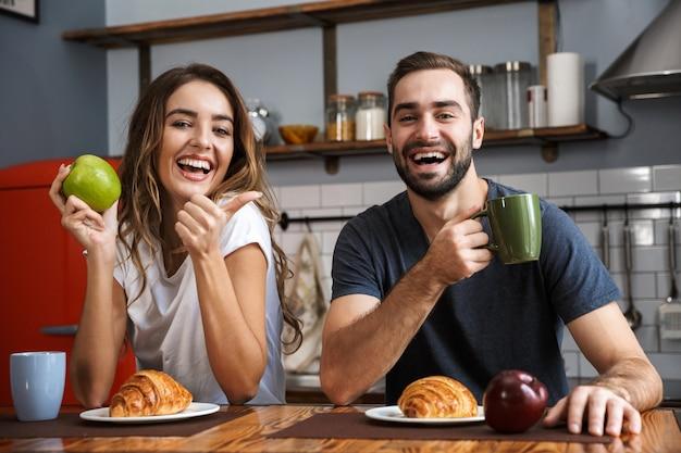 Beautiful cheerful couple having breakfast at the kitchen