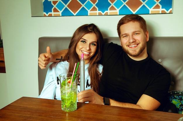 술집에서 아름 다운 명랑 커플 흡연 shisha 및 음료 칵테일 앞에 미소