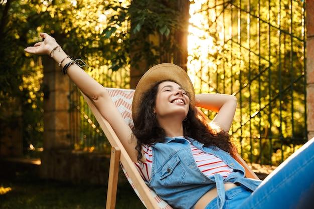 Красивая веселая кудрявая женщина на открытом воздухе в парке отдыхает