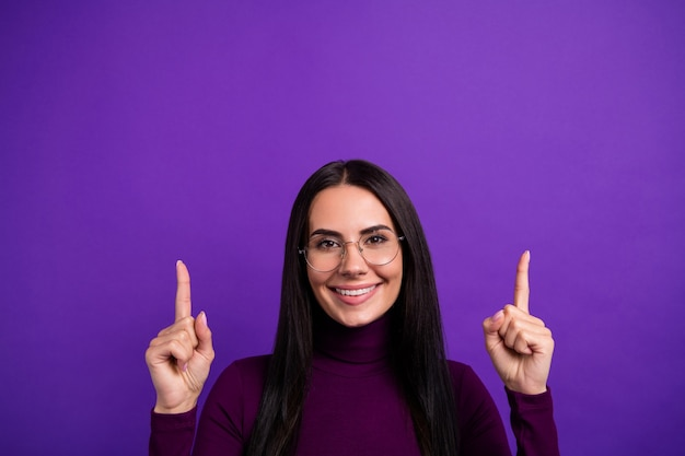Beautiful cheerful cute nice pretty woman pointing up smile toothy gesturing for you to notice new information isolated vibrant purple color wall