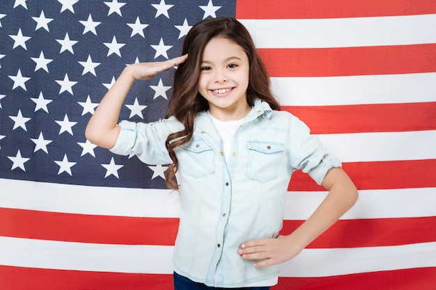 Красивая веселая довольная девушка веселится и выражает радость, стоя против американского флага