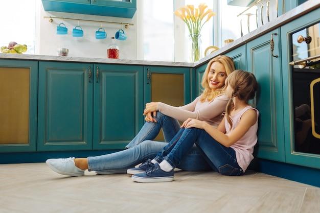 笑顔でキッチンの床に座って抱きしめる美しい陽気な金髪の母と娘