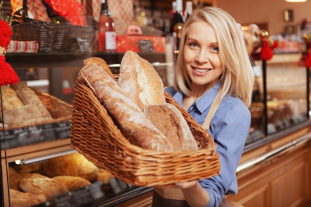 Beautiful cheerful female baker holding out basket full of delicious fresh bread