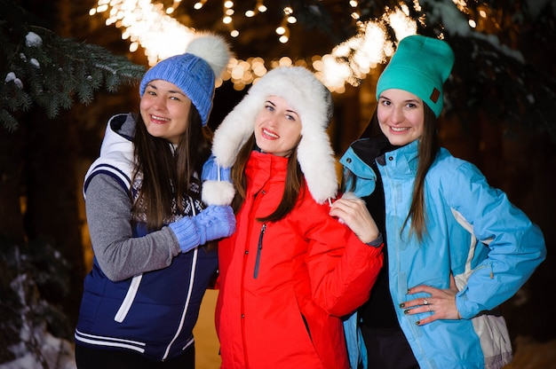 Beautiful cheerful female friend in colorful jackets having fun and walking in the city street at night at christmas time.