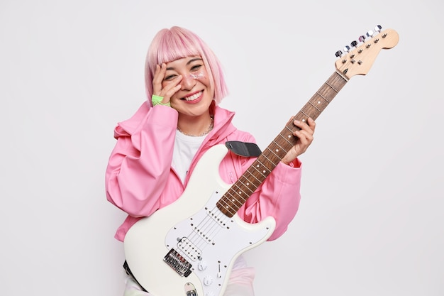 Beautiful cheerful female musician plays electric guitar being member of popular rock group has pink hairstyle wears jacket