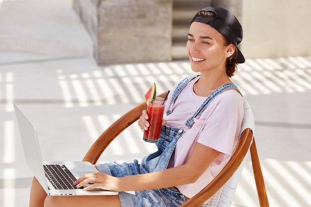 Bella donna allegra in berretto alla moda, vestita in abiti alla moda, beve frullato fresco, cerca informazioni sul computer portatile