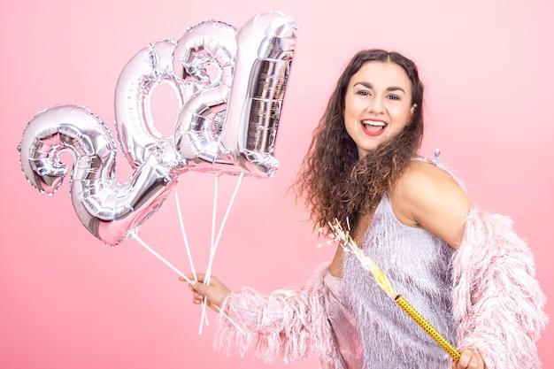 Bella ragazza bruna allegra vestita a festa con i capelli ricci su uno sfondo rosa studio in posa con una candela di fuochi d'artificio in mano e palloncini d'argento per il concetto di nuovo anno