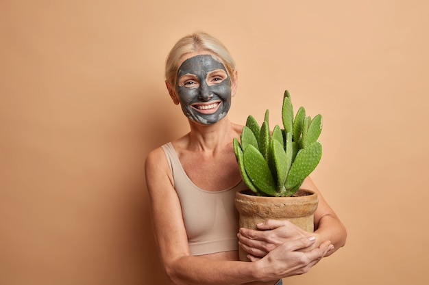 Beautiful cheerful forty years old european woman applies beauty mask for reducing wrinkles has positive expression wears cropped top carries potted cactus poses indoor