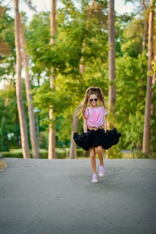 Beautiful cheerful girl in a fluffy tutu skirt in sunglasses with a long tail of hair dances and smiles