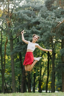 A beautiful cheerful girl in a red skirt jumped high in the park on the grass and smiles
