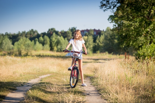 Beautiful cheerful girl riding bike in meadow at sunny day