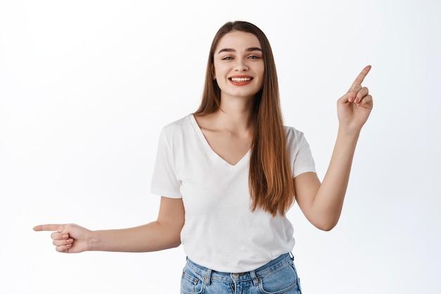 Bella ragazza allegra, sorridente e danzante, puntando il dito lateralmente su due offerte promozionali, mostrando le scelte di banner, le migliori offerte promozionali, in piedi sul muro bianco
