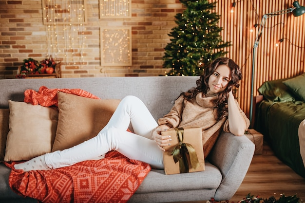 自宅で新年の木のソファにクリスマスプレゼントと美しい陽気な幸せな少女