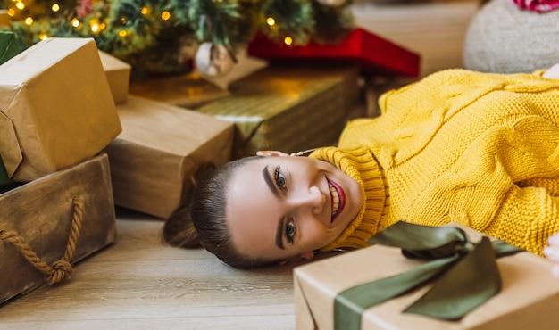 집에서 새 해 나무의 배경에 크리스마스 선물과 함께 아름 다운 쾌활 한 행복 한 어린 소녀
