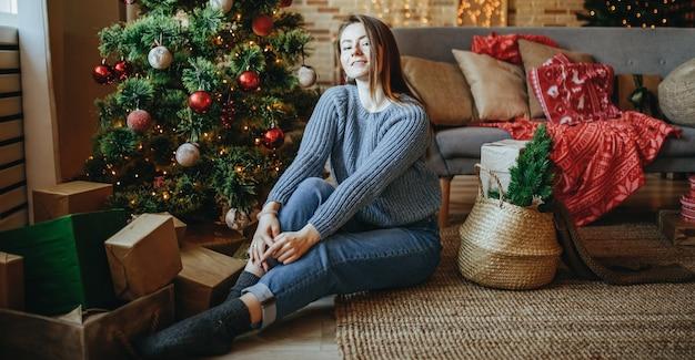 自宅の新年の木の近くの床にクリスマスプレゼントと美しい陽気な幸せな少女
