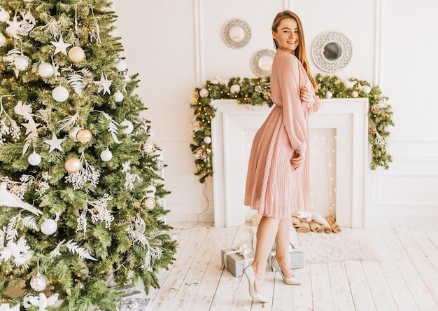 自宅で新年の木の上のクリスマスプレゼントと美しい陽気な幸せな少女