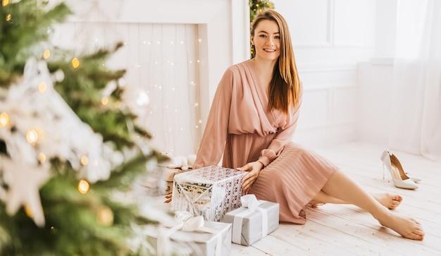 Красивая веселая счастливая молодая девушка с рождественскими подарками