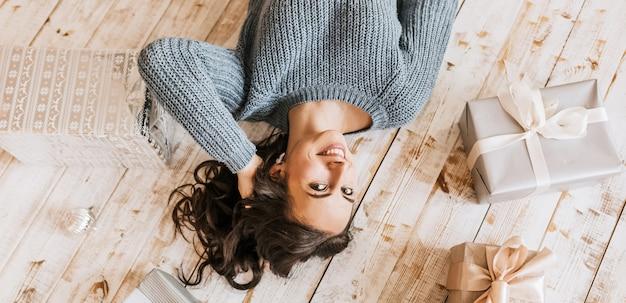 Красивая веселая счастливая молодая девушка с елочными игрушками и подарками на деревянном полу
