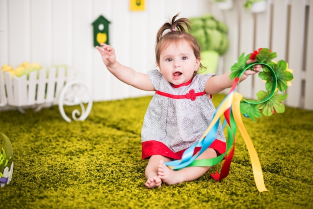 Beautiful cheerful little girl in a dress sits on rug in her cozy children's room and plays with flowers.