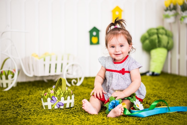 Beautiful cheerful little girl in a dress sits on rug in her cozy children's room and plays with flowers