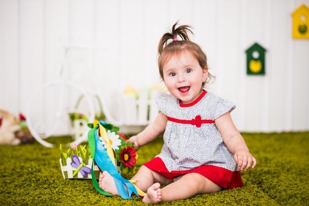 Красивая веселая маленькая девочка в платье