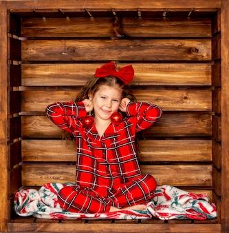 Красивая веселая маленькая девочка в красной клетчатой рождественской пижаме с елочными шарами на деревянном фоне