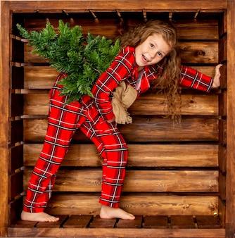 Красивая веселая маленькая девочка в красной клетчатой рождественской пижаме с маленькой елкой в руках на деревянном фоне
