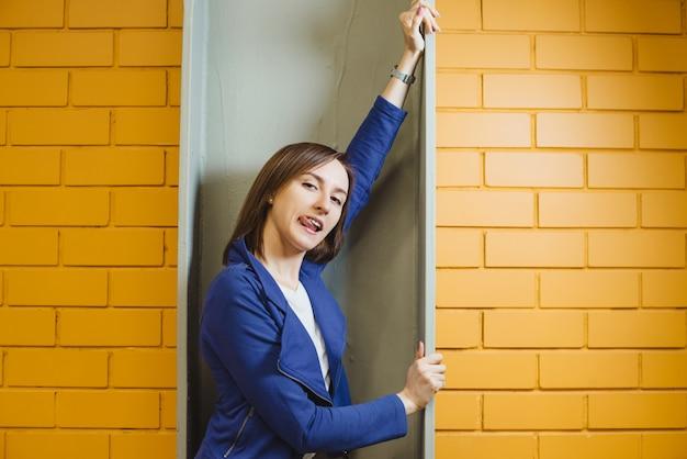 Красивая веселая современная сумасшедшая блондинка показала свой язык на фоне желтой кирпичной стены