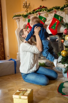 Beautiful cheerful mother playing with her 1 year old baby son at christmas tree