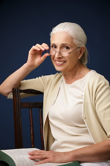 Beautiful cheerful old woman reading book.