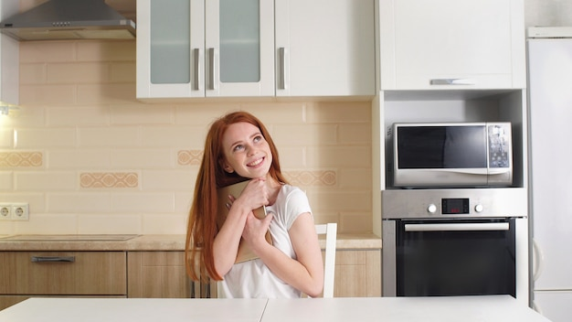 Beautiful cheerful redhead girl hugs her tablet with happiness