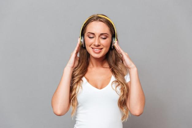 헤드폰과 눈으로 음악을 듣고 아름다운 밝은 웃는 여자는 회색 벽에 고립 폐쇄