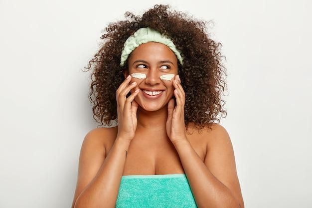 Bella donna allegra applica la crema cosmetica per la cura del viso, guarda volentieri da parte, indossa la fascia, si trova avvolto in un asciugamano, si preoccupa dell'aspetto e della bellezza