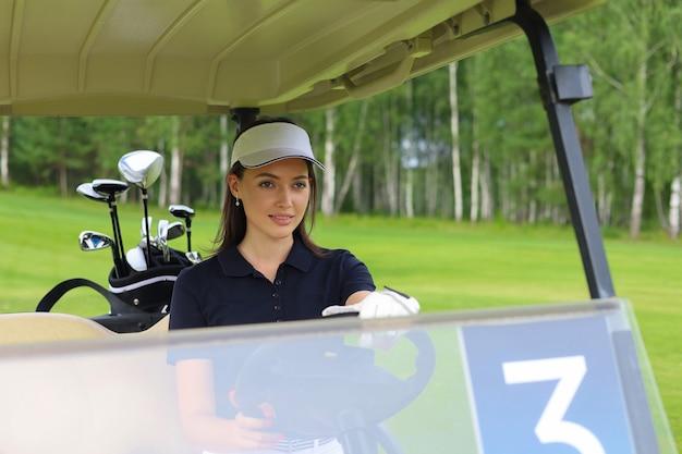 ゴルフカートを運転する美しい陽気な女性。
