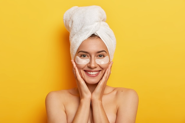 Beautiful cheerful woman has wrappped towel for drying hair, keeps both hands on cheeks, smiles gently, has fresh skin, cares about complexion, wears patches under eyes