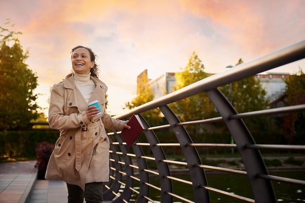 베이지색 트렌치 코트를 입은 아름다운 쾌활한 여성은 따뜻한 가을날의 아름다운 일몰을 배경으로 책과 테이크아웃 종이컵을 들고 공원에서 뛰놀며 자유를 만끽합니다. 가을 주말