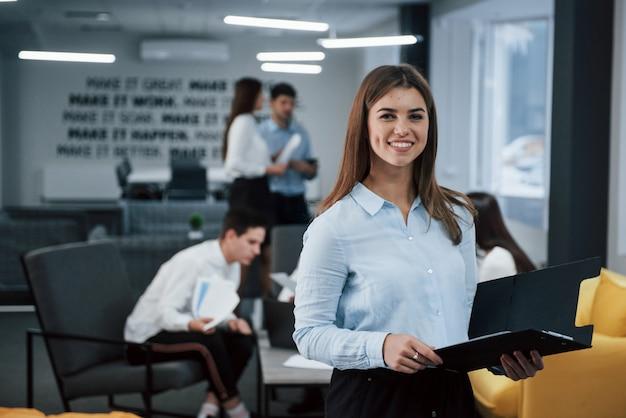 美しい陽気な女性。バックグラウンドで従業員とオフィスに立っている若い女の子の肖像画