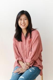 Beautiful cheerful woman sitting by a white wall