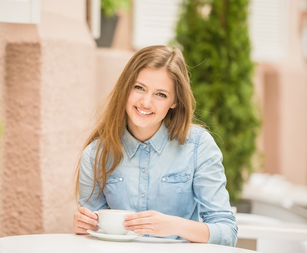 Beautiful cheerful woman sitting in summer cafe.