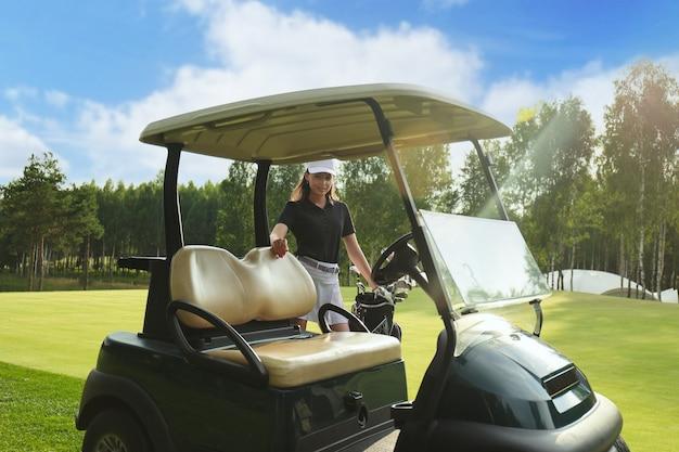 ゴルフカートの近くに立っている美しい陽気な女性。