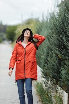 Красивая веселая женщина идет по переулку в осеннем пальто.