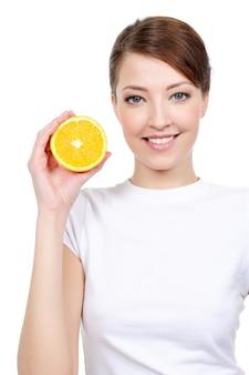 Красивая веселая женщина со свежим апельсином возле ее лица