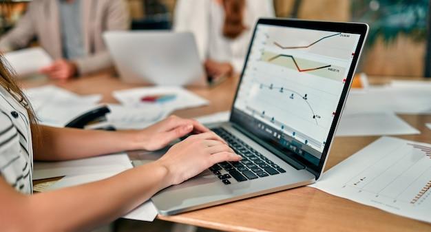 Красивая веселая женщина, работающая на ноутбуке, сидя за офисным столом со своими коллегами.