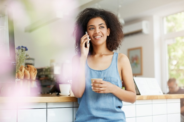 Beautiful cheerful young african woman student smiling talking on phone drinking coffee in cafe.