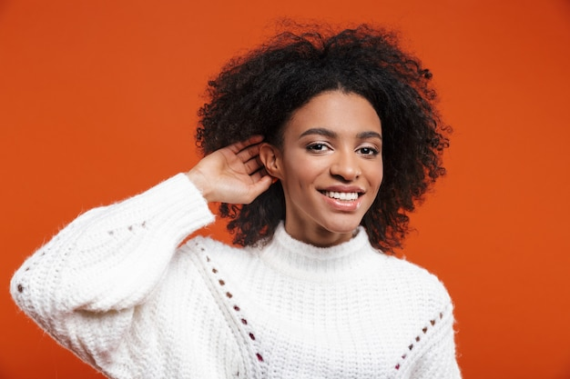 Beautiful cheerful young african woman wearing sweater standing islolated over red wall, trying to hear rumors