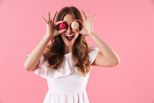 ピンクの壁に孤立して立っている夏のドレスを着て、おいしいマカロンを保持している美しい陽気な若いブロンドの女の子