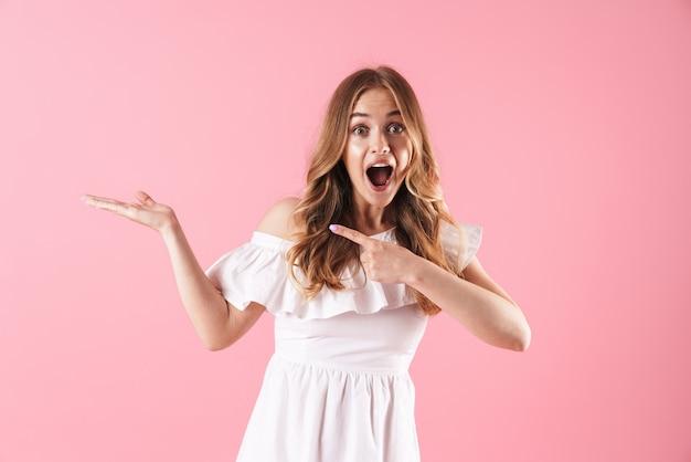 ピンクの壁に孤立して立っている夏のドレスを着て、離れて指している美しい陽気な若いブロンドの女の子
