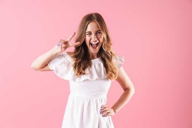 ピンクの壁に孤立して立っている夏のドレスを着て、平和のジェスチャーを示す美しい陽気な若いブロンドの女の子